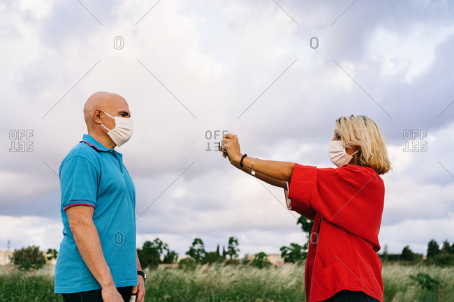 Positive female in face mask taking picture of husband in casual wear using photo camera while spending summer weekend together in countryside during coronavirus epidemic