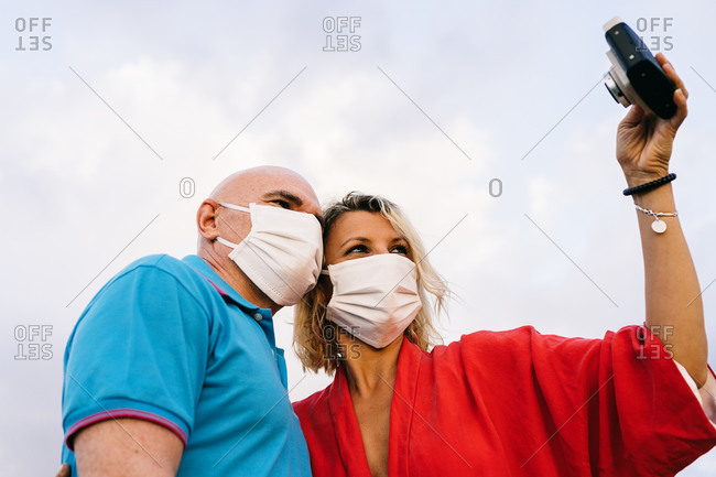 Content adult couple in face masks wearing casual summer clothes standing taking selfie on mobile phone while spending evening in nature