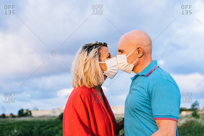 Side view positive adult couple in casual clothes wearing protective respirators and kissing through masks while spending summer evening in countryside