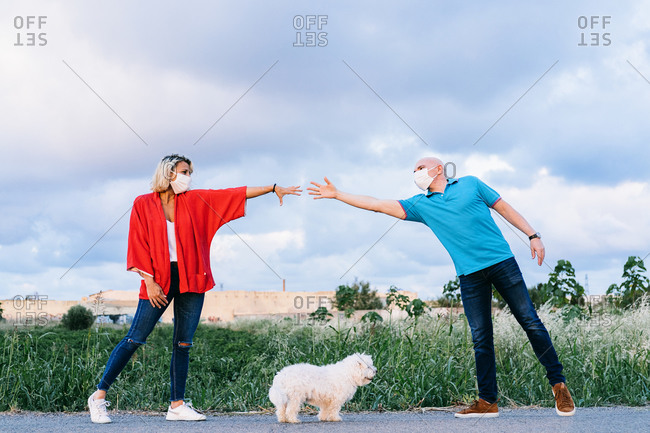 Romantic couple in respirators and casual clothes reaching hands while standing together in countryside looking at each other with love with cute bichon frise dog on the floor under their arms
