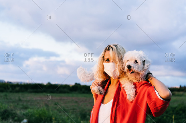Positive female in casual clothes wearing protective face mask standing with funny white Bichon Frise dog on shoulders against blurred summer countryside landscape during coronavirus outbreak