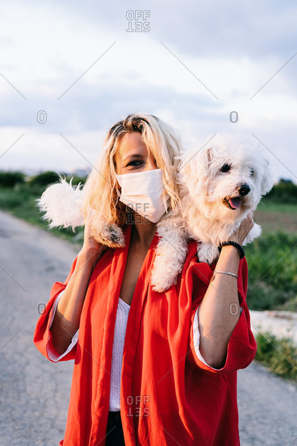 Positive female in casual clothes wearing protective face mask standing with funny white Bichon Frise dog on shoulders against blurred summer countryside asphalt road landscape during coronavirus outbreak