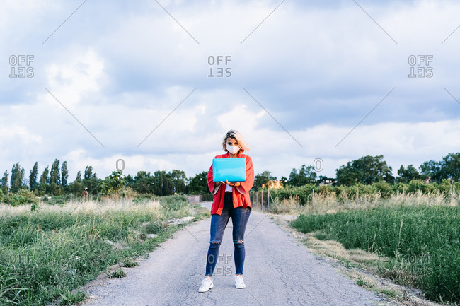 Full length calm female in casual clothes and medical mask using modern netbook while standing on gravel road in countryside