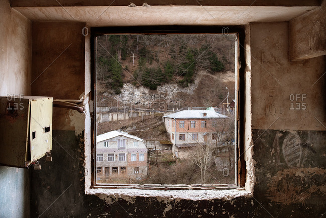View of residential buildings on hill through shabby window of abandoned house with scratched walls