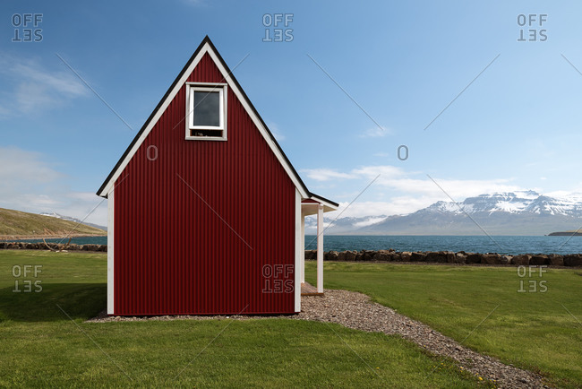 Small wooden cabin located on green lawn on background of lake and mountain ridge on sunny day under blue sky
