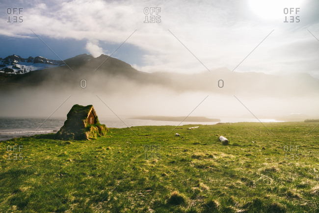 Spectacular scenery of small shack covered with moss and located near lake and mountain in foggy morning