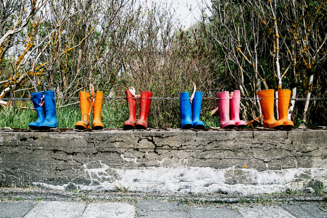 Pairs of colorful rubber boots on metal chain placed along stone fence in countryside