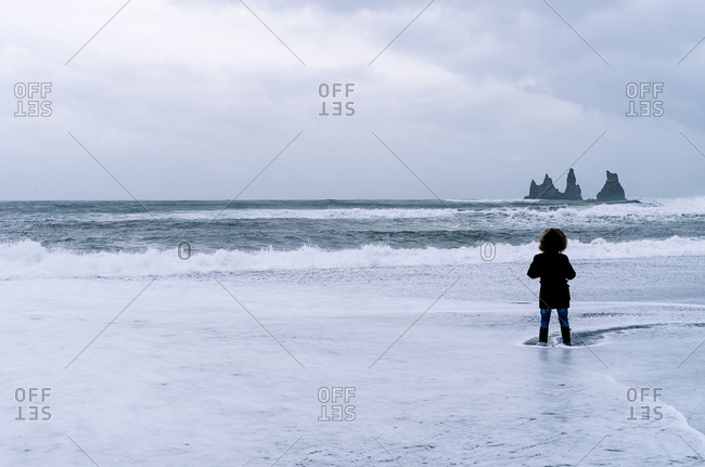 Back view of tourist in warm clothes standing on seashore in water and admiring rocky landscape