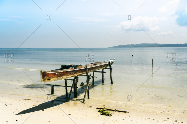Shabby fishing boat moored on seashore and placed on wooden sticks in water against blue sky