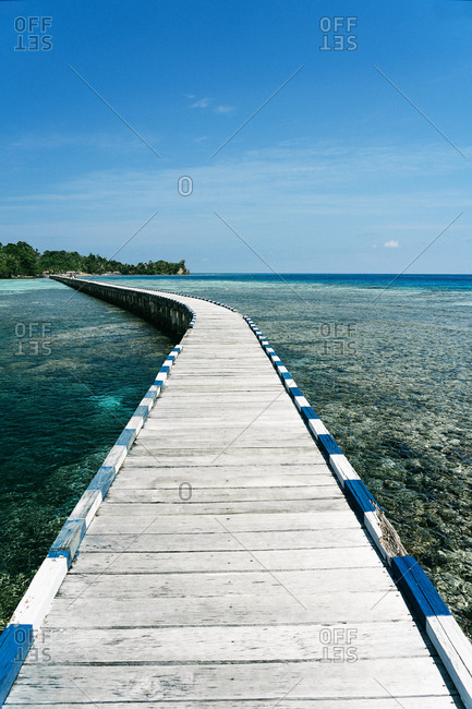 Long wooden embankment going through clear water of sea on sunny day in summer