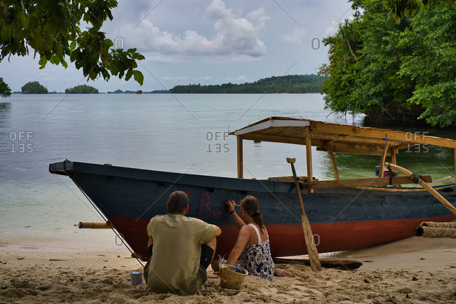 Back view of unrecognizable couple sitting on sandy beach at seaside and writing on boat with red paint
