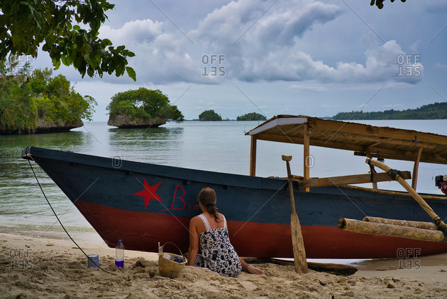 Back view of anonymous female in dress painting on wooden boat with red color while sitting on seashore