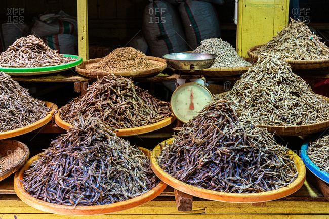 Piles of delicious dried anchovy on plates placed on stall at local fish market