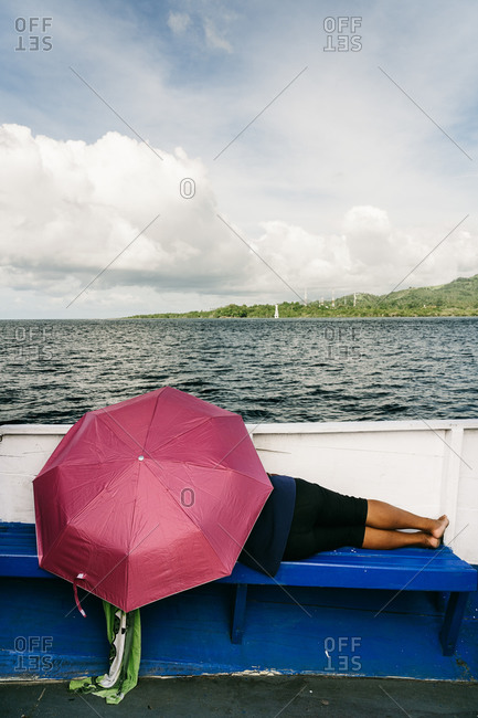 Back view of unrecognizable ethnic person lying under umbrella on wooden bench at seafront and relaxing during daytime
