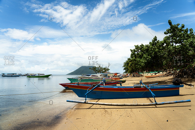 Collection of wooden boat moored on sandy coast on background of majestic seascape and mountain on sunny day