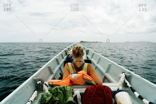 Back view of anonymous female traveler sitting in boat and floating on calm sea water while enjoying vacation in summer