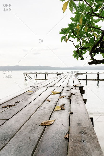 Shabby wooden quay in clean water of pond on background of mountains on overcast day