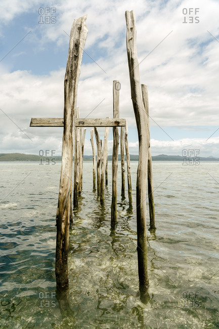 Shabby wooden poles placed in clear water of sea on sunny day on background of blue sky