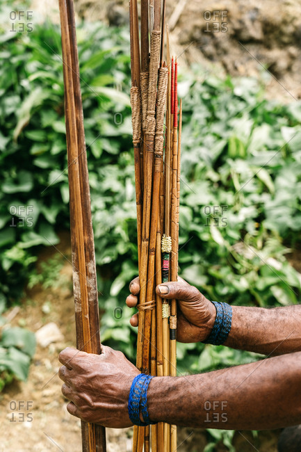 Unrecognizable crop ethnic male from tribe standing with collection of handmade bamboo arrows in green forest