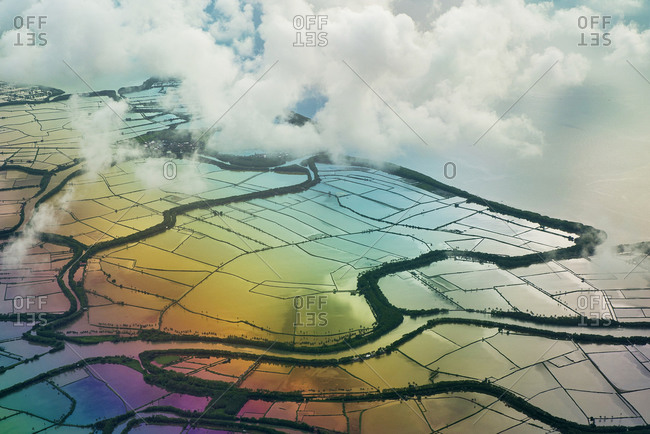 Spectacular drone view of agricultural rice paddies with water reflecting colorful sky and clouds