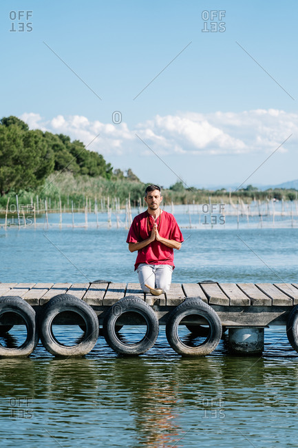 Peaceful man in comfy clothes sitting on wooden pier of sea and meditating in Hero yoga pose with namaste gesture