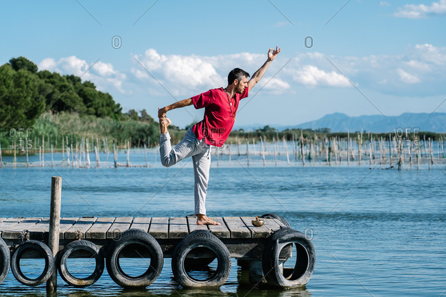 Full body of peaceful barefooted guy in casual wear performing Lord of the Dance yoga pose and  Gyan mudra on lumber pier on sunny day