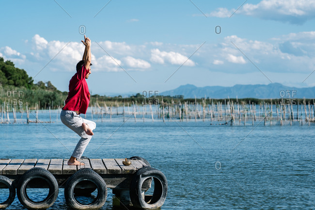 Side view of unrecognizable male in casual clothes performing Eka Pada Utkatasana posture during morning yoga session on wooden quay against calm sea
