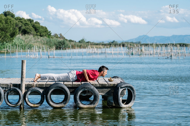 Peaceful man in comfy clothes lying down on wooden pier of sea and meditating