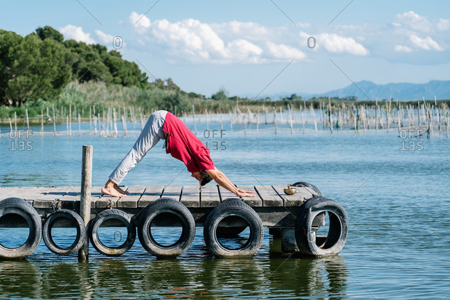 Full body of peaceful barefooted guy in casual wear performing yoga pose on lumber pier on sunny day