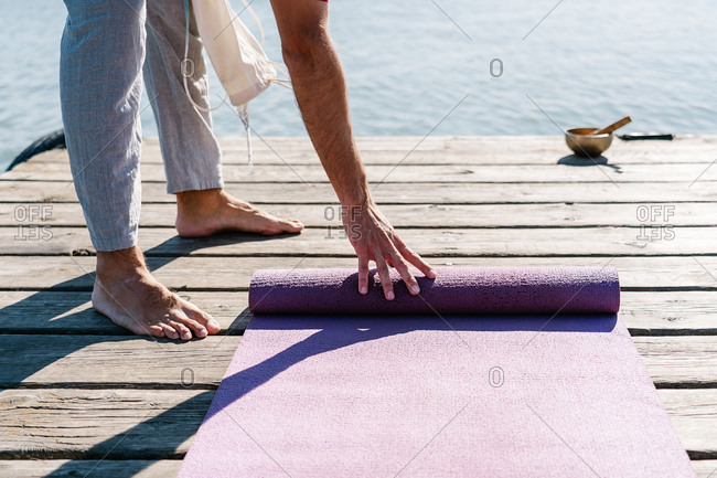 Crop of side view of barefooted man in casual wear holding yoga mat and singing bowl getting ready practicing meditation on wooden embankment against rippling sea