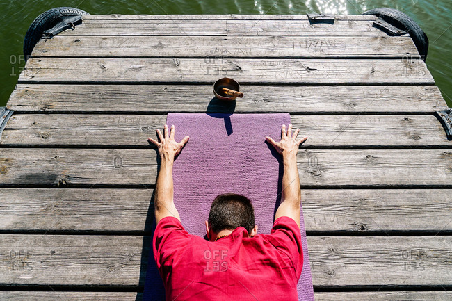 From above back view of anonymous male in casual clothes recreating in Extended Child pose during yoga session on wooden quay near sea on sunny day