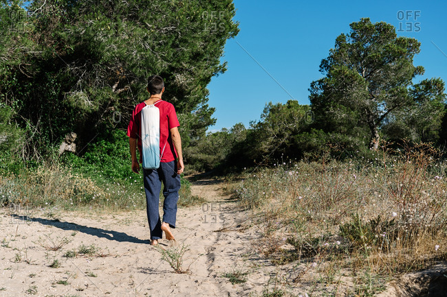 Back view of unrecognizable barefooted male in casual clothes and yoga mat bag walking along sandy pathway among green trees against cloudless blue sky