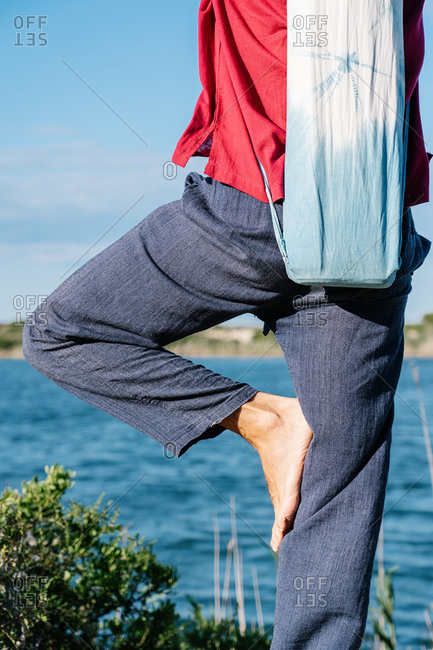 Crop unrecognizable barefooted person with yoga mat bag standing in Vrksasana pose against calm sea on sunny day