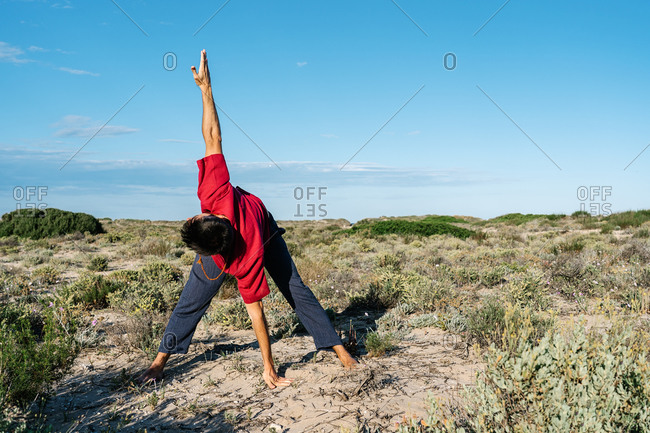 Full length of anonymous man in casual clothes standing on sandy terrain and doing Revolved Wide Legged Forward Bend asana during outdoor yoga training