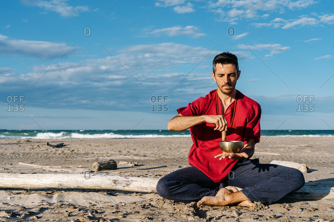 High angle of peaceful young barefooted male in casual clothes sitting on sandy beach in Half Lotus asana near waving ocean and playing Tibetan singing bowl against blue sky