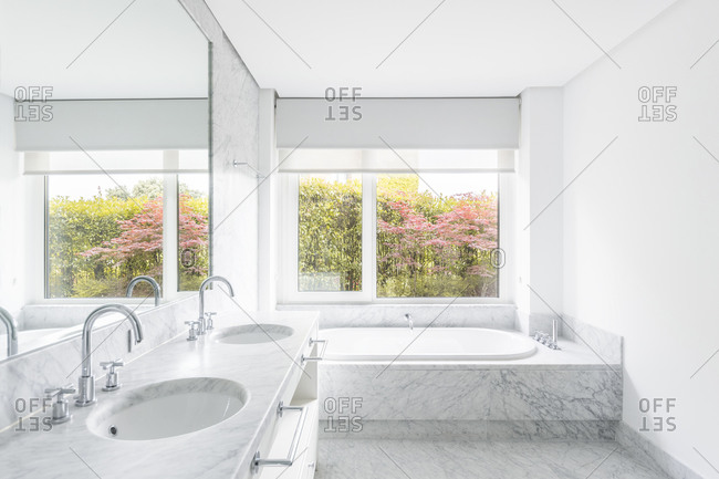 Creative minimalist design of bathroom with similar vanity units under big mirror and bath tube near window overlooking shrubs with blooming flowers