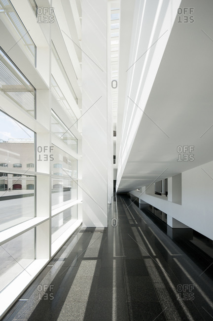 Contemporary style of house with empty narrow corridor and white smooth walls in front of rectangular window in sunlight