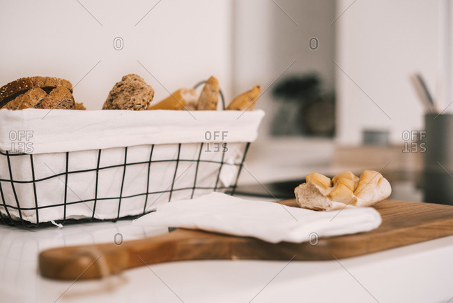 Side view of fresh assorted cut bread and buns served in tray and on wooden cutting board on white table during breakfast
