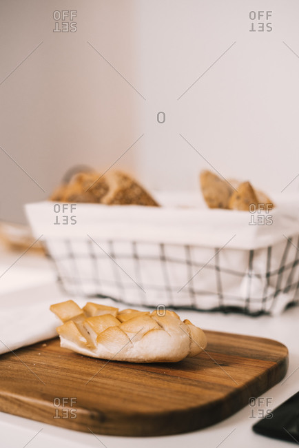 Fresh assorted cut bread and buns served in tray and on wooden cutting board on white table during breakfast