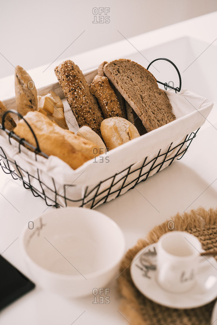 Porcelain tableware set arranged on cloth napkin near basket with fresh bread on table served for breakfast in cozy light apartment