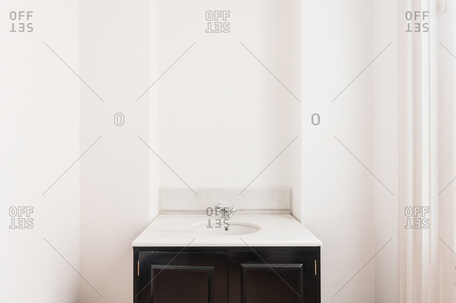 Open wooden door with ornament and golden knob in modern bathroom with square shaped vanity unit with round sink and stainless steel tap near white wall