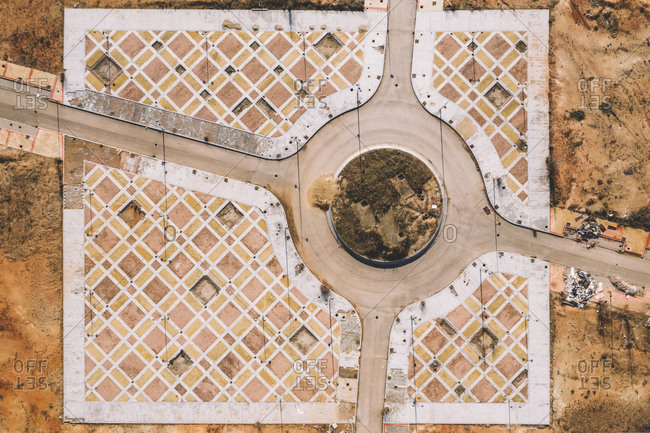From above aerial view of road intersection with traffic roundabout in dry terrain with ornamental infrastructure
