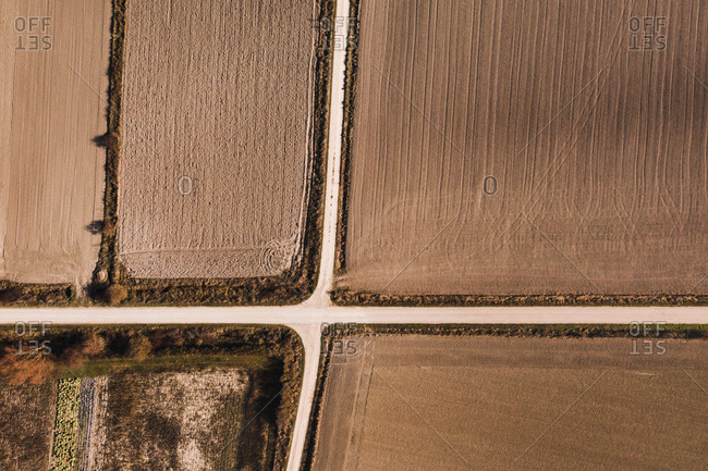 From above aerial view of crossroads going through agricultural field in rural area in summer day