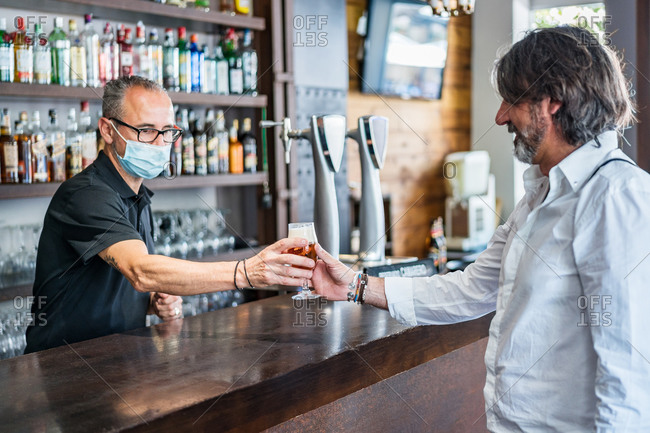 Ethnic male bartender on medical mask giving glass of beer to aged gray haired man while working in bar at daytime