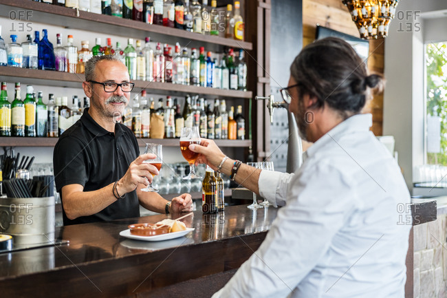 Aged man clinking glasses of bear with bearded barkeeper in black t shirt while having lunch in pub