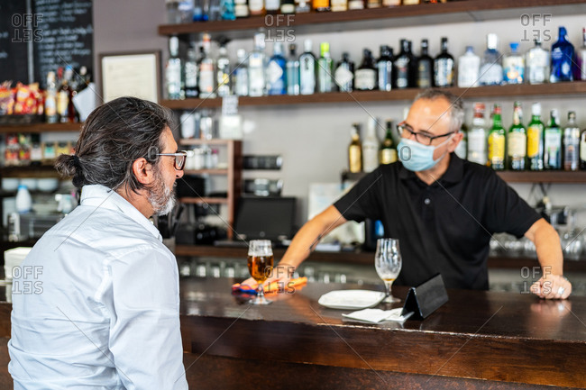 Ethnic gray haired barman in eyeglasses and mask making clean bar counter while talking to senior male client that drinking beer