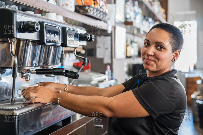 Side view of positive ethnic barista pouring hot coffee into cup from coffee machine while working in bar