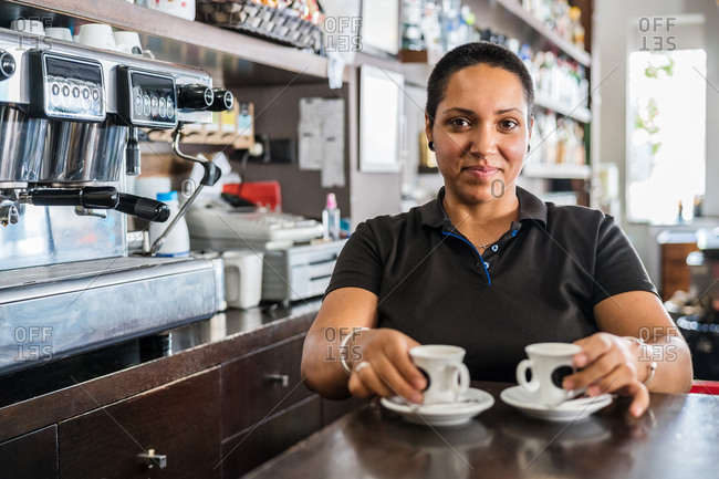 Smiling ethnic female worker in black uniform standing at bar with cups of coffee at daytime