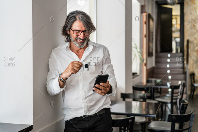Positive ethnic aged bearded gray haired man browsing smartphone and having coffee while leaning on wall in empty cafe at daytime