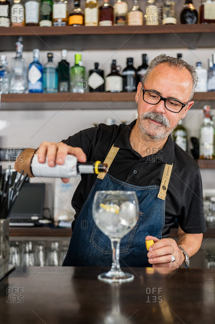 Senior ethnic focused bartender pouring cold alcohol into glass with ice and lemon while making cocktail at bar